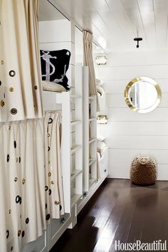 Your guests would get a kick out of a room like this. The bunk room feels like a ship's cabin and is lined with six bunks, four on one side and two on the other in a Marin County, California, house designed by Erin Martin and owner Kim Dempster. Grommets on the curtains are meant to evoke bubbles. The brass porthole mirror was in Dempster's house when she was a child. Alec Hemer  - HouseBeautiful.com
