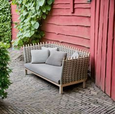 red clapboards, brick patio and outdoor sofa by Paola Lenti