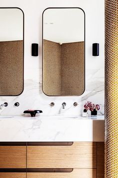 We love the repetition of curves in this bathroom. From the curvaceous vanity mirrors to the cylindrical sconces, penny round tiles, and rounded vanity pulls, this bathroom is feminine yet minimal.