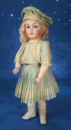 """22"""" (55 cm.) Bisque socket head,blue glass sleep eyes,mohair lashes,painted lashes,brush- stroked brows with feathering detail,accented nostrils,closed mouth,shaded and outlined lips,blonde mohair wig,composition and wooden ball-jointed body. Condition: generally excellent. Marks: K*R Simon & Halbig 117 55."""
