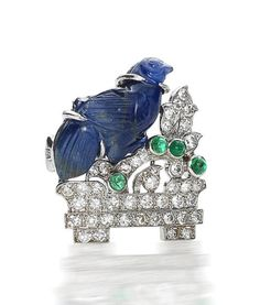 A diamond, emerald and carved sapphire brooch, by Cartier, circa 1935  The carved sapphire bird seated on a plinth amongst foliage, set throughout with single-cut diamonds and highlighted with cabochon-cut emeralds, diamonds approximately 1.00 carat total, signed Cartier London, height 2.5cm