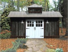 Shed with dark grey wood siding and white doors.