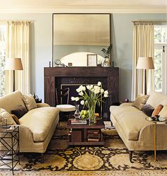 LOVE the contemporary lines and feel mixed with traditional elements. The modern mirror, mantle, accessories on the mantle and the coffee table.
