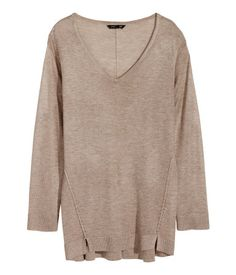 Soft, fine-knit sweater with visible seams, pointelle details, and a V-neck. Small slits at sides.