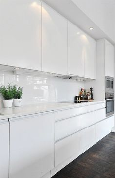 White kitchen.  Like this kitchen, white gloss units white worktop and dark oak floor.  Not sure on handles though as they look quite cheap.