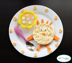 chicky from meet the dubiens blog      Chickie - white cheddar rice cake, carrot details and icing eyes.  Flower silicone muffin cup with unsweetened strawberry kiwi applesauce with a few sprinkles.  Sliced cheesestring around the plate.