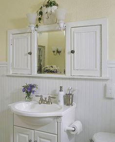 One way to declutter the top of your bathroom sink is to add a cabinet that can store odds and ends.  Here, two medicine cabinets (fitted with wood doors instead of mirrors) double the storage. The shallow vanity allows extra walking space yet provides some bathroom storage.