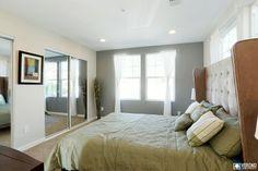 Mirrored closet doors. White curtains. Grey walls.