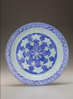 Charger | Origin:  Iran | Period: mid-15th century  Timurid period | Details:  Timurid production of blue-and-white ceramics flourished in fifteenth-century Iran. The decoration of this large molded plate centers on a wheel-like motif. Its stylized octafoil design of alternating scale and wave patterns was adapted from Chinese models.