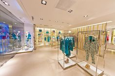 Liu Jo Concept Store. The alternation between gold, steel and wood, and the presence of semi-transparent screening contributes to creating balanced subdivisions between different shopping areas, making for a more suggestive shopping mood. Retail design by Fabio Caselli Design