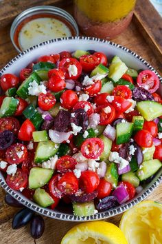 A Greek salad with tomatoes, cucumber, onion, olives, feta and Greek dressing.