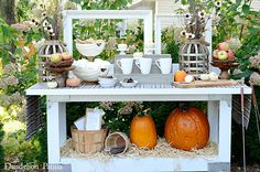A tiered pumpkin tray, filled with graham crackers and marshmallows, adds to the rustic theme of this outdoor s'mores station.