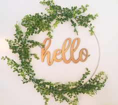 A modern and simple wreath for spring and summer 2017!   This new and original wreath is made on a silver/metal 19 hoop. I have added greenery and a wooden Hello word, painted gold, that hangs in the middle with a clear line. When hung, especially in a window, the wooden word appears to float invisibly!  So beautiful and yet perfectly simple and modern, ideal for ANY decor!  Finished wreath approx 20 across   ***Materials may be substituted with similar greenery as supplies are available...