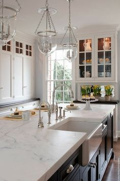 cabinets to the ceiling...white countertops and mirror backsplash reflects flowers...