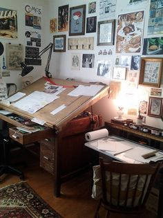 Surround yourself in inspiration! Love this drafting table accompanied by walls covered in artwork.