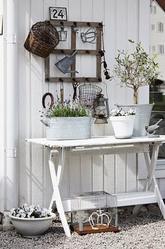 Love this trend of making little room-like areas outside!  Window pain with hooks to hang garden tools and baskets, and a wooden table with plants on it