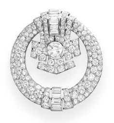 A DIAMOND BROOCH, BY VAN CLEEF & ARPELS   Designed as a circular and baguette-cut diamond openwork geometric plaque, centering upon a larger circular-cut diamond, mounted in platinum, (with additional pendant clip)  Signed Van Cleef & Arpels, N.Y., no. 960