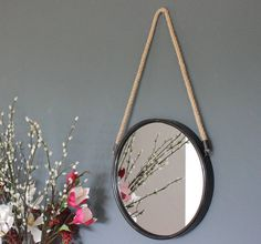 A lovely solid round mirror hung on a rope.Available in soft washed wood or black metal.These mirrors are sold separately, but look great as a set too. One is in a soft white washed wood and the other a black metal. They add a funky feature to a wall and would also make a great addition above a sink or desk. They are easy to hang and are a good size individually for smaller spaces.wood or metal.black metal : H: 660mm Dia: 350mm White washed wood : Dia: 280mm
