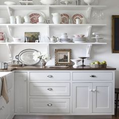 Open shelves grant easy access to vintage red transferware, as well as whiteware from Macy's in this country farmhouse.
