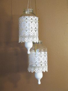 Hanging jar lanterns - use perforated scrapbook paper, lace and a wooden finial painted white. Hang with wire and put votives inside. I think this would look even better if the jars were painted with glass paint and the white paper, lace and finials were painted metallic gold!