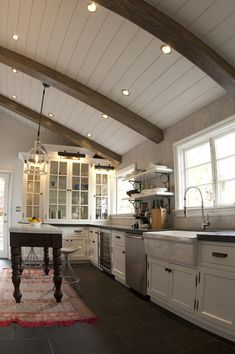 15 Rustic Kitchen Design Photos: slant ceiling,large window over sink,white,glass cabinet doors,wrought iron