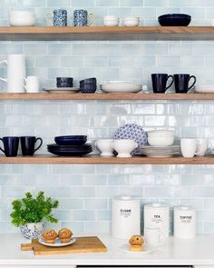 Open kitchen shelving with light blue subway splash back.