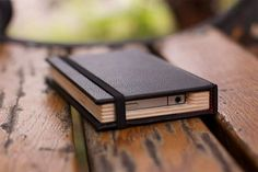 Little Black Book iPhone Case  The illusion of intellect, classic style, a unique accessory: these are all things we want. The Little Black Book iPhone Case meets all these secret little desires, while keeping your iPhone 4 stashed in a safe, sturdy case. It looks & feels like a Moleskine notebook until you open it, where your iPhone resides in a cutaway wood cradle