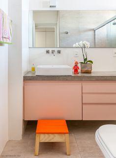Pisos e parede revestidos de porcelanato que imita cimento queimado, bancada de concreto e marcenaria laqueada em um tom de rosa.