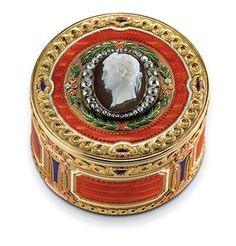 A Three-Colour Gold, Hardstone and Guilloché Enamel Box by Fabergé, workmaster Michael Perchin, St Petersburg, circa 1890 Circular, the sides with panels of translucent orange over a wavy guilloché ground within white borders, alternating with lozenges of blue enamel, the cover set with an oval sardonyx cameo, finely carved with a bust of an emperor, possibly Alexander I, surrounded by graduated diamonds, all within bands of ribbon-tied laurels, chased flower-heads and guilloché enamel.