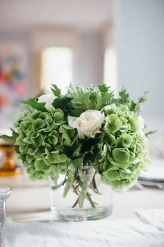 Use Simple and Seasonal Florals  Chicago florist Molly Flavin created simple, seasonal, unfussy arrangements using ornamental kale, green hydrangea, seasonal greens, and white roses. Claire recommends using three medium size arrangements for a typical table of eight and adding in a pop of color with a few one- and two-stem arrangements for a less formal look. Keeping the flowers in low containers encourages conversation at the table.