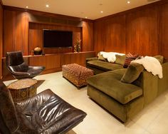 The wall paneling in this exotic basement space is Hawaiian ohia wood, which gives the space the look of either midcentury modern or Asian design. The earthy tones of the contemporary sectional sofa and leather chair and the global-inspired prints of the ottoman and side table create a chic space for the homeowner who loves to entertain.