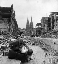 German woman with all her worldly possessions on the side of a street amid ruins of Cologne, Germany. 1945