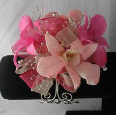 Bold Hot Pink & Light Pink Dendrobium Orchids wrest on a bed of silver glitter & hot pink ribbon.  Shown here on our 	 Serendipity corsage bracelet.  $30.99 	 The Secret Garden in Decatur Illinois wants to be your prom corsage & boutonniere headquarters.  Come and visit our corsage bar to create your own one of a kind corsage!