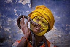 A boy celebrating Holi holds his pet snake in this National Geographic Your Shot Photo of the Day.