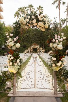 An artful archway added floral flair to this outdoor @Mandy Dewey Seasons Hotel Los Angeles at Beverly Hills wedding aisle.