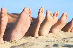 Feet relax at beach. Closeup of feet row lying in line at summer beach ,