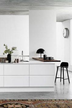 Cozinha americana branca moderna decorada com tapete e piso de cimento