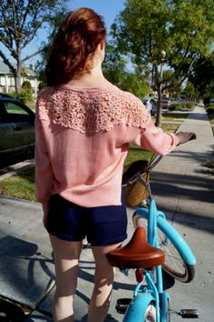 Give'em something to talk about with this knitted cropped sweater topped with an open crochet yoke. Skip accessories and just wear your hair up so that all can see from front to back the whimsical floral design. The coral pink tone makes for a pretty and girlie softness, while the black becomes quite the bold show stopper. The sleeves are long and have a slight pouf, giving it an elegant touch.