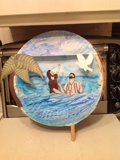 John the Baptist baptizing Jesus.  Jesus is on a Popsicle stick to move.  Large paper plate for background and smaller paper plate cut in two for foreground ...painted..: