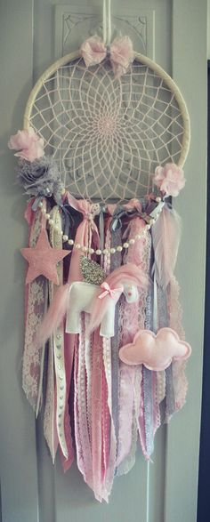 Beautiful Bohemian inspired dream catcher. Handmade using crocheted cotton, soft lace in grey, white & blush pink colours, ribbon and embellishments including a string of pretty pearls, felt unicorn, cloud and glitter star! 25cm hoop binded in a natural cotton ribbon and a mini handmade clay heart with the words Somewhere over the Rainbow Lace hangs approx 50cm downwards from bottom of the ring. Hang from a bed knob, window or wall to add a touch of bohemia to your chosen room. Larger &am...