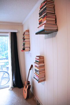 Buy simple metal L-shaped brackets, screw them in the wall and start stacking! No glueing or ruining books.