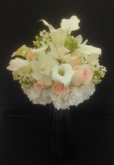 White was the star of this beautiful bride's bouquet, which showcases white hydrangeas, calla lilies, and star of Bethlehem. Pink and peach roses provide a soft accent against the white.  See more wedding bouquets, centerpieces, and more at www.jeffmartinsweddings.com