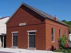"""The African Methodist Episcopal Church on East Fifth Street, in Madison, IN included noted Underground Railroad participants George DeBaptiste, Elijah Anderson, Griffin Booth, Joseph O'Neal, and David Lott. The building is a modest, one story, Greek Revival design with elongated windows along the side walls and two double doors with transoms and flat stone lintels on the facade. A stone marker within the façade's brick course reads """"AME Church, Founded 1850."""""""