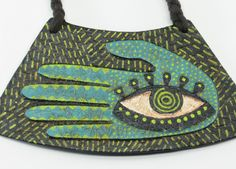 This is a very cool piece, and it comes from a very cool shop. Take the time to look. Very cool. -- Folk art hamsa bib collar upcycled recycled by greendivadesigns