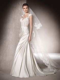 Das Brautkleid MERCY im Prinzessin-Stil besticht durch seinen drapierten Satinrock. Oberteil aus Tüll, Garnstickerei und Spitze mit Schmucksteinbesatz. U-Boot-Ausschnitt und herzförmiges Dekolleté