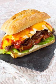 Royale hamburger met de naam Chivito. Gerecht uit Uruguay. Brood met gebakken biefstuk, ei, tomaat, sla, kaas en gebakken uien. Een keertje bijzonder mag.