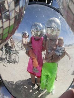 A very modern family reflected in Kirsten Berg's spherical art work on the playa at Burning Man by Christopher Michel
