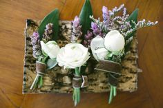 purple and white floral boutonnieres with brown velvet ribbon - photo by Vis Photography