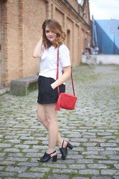 Look short moletom preto, camiseta branca com brilho, bolsa vermelha Gucci, sandália de salto com tachas preta.