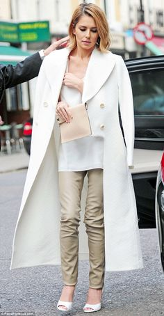 Going for the godfather look: Cheryl arrived with her coat resting on her shoulders on the...